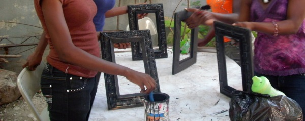 Young Haitian women painting picture frames at KOFAVIV in Port-au-Prince, Haiti