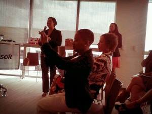 Leticia Barr (standing), Jazzy Jones (with camera) and Xina Eiland (seated) at BlogaTech 2013